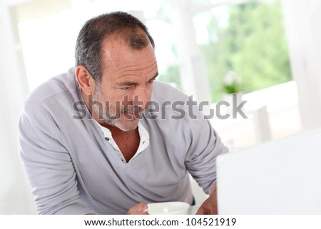 Senior man connected on internet with laptop at home