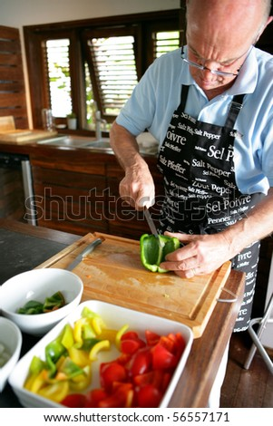 Senior man cutting a green pepper - stock photo