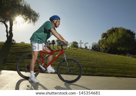 Senior man cycling in park at dusk side view
