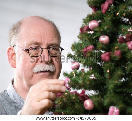 Senior man decorate Christmas tree - stock photo