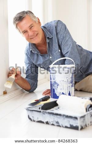 Senior man decorating house - stock photo