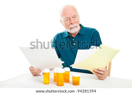 Senior man depressed by a pile of medical bills.  Isolated on white. - stock photo