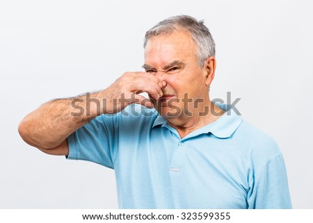 Senior man doesn't like how something smells.Unpleasant smell