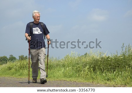 Senior man doing a Nordic Walk on a sunny day. - stock photo