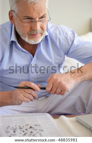 Senior man doing crosswords in sofa