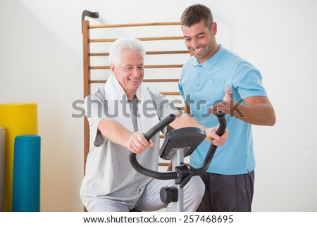 Senior man doing exercise bike with his trainer in fitness studio - stock photo