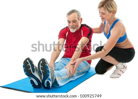 Senior man doing fitness exercise with help of trainer at sport gym - stock photo