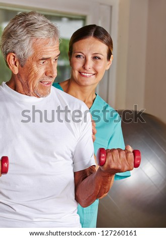 Senior man doing rehab sports in nursing home with a physiotherapist - stock photo