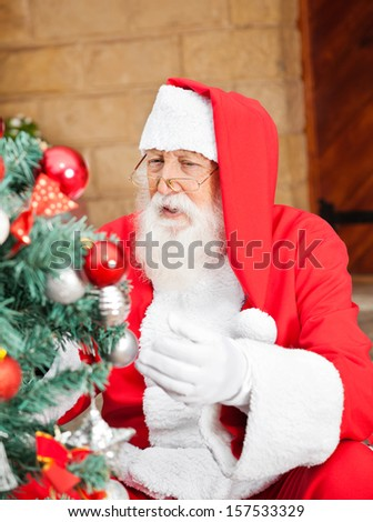 Senior man dressed as Santa Claus decorating Christmas tree outside house - stock photo