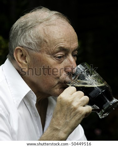Senior man drinking a beer outside of pub. - stock photo