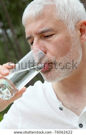 Senior man drinking fresh water - stock photo
