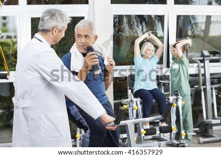 Senior Man Drinking Water By Doctor In Fitness Studio - stock photo