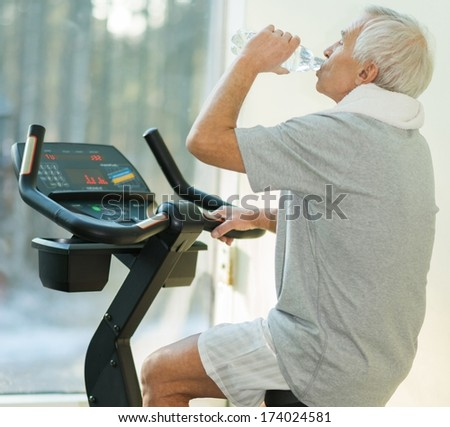Senior man drinking while doing exercise on a bike in a fitness club - stock photo