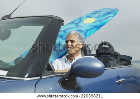Senior man driving a convertible with a surfboard in it - stock photo