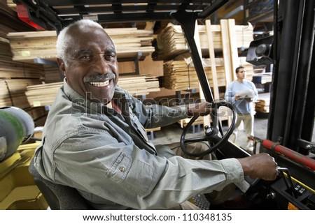 Senior man driving forklift - stock photo