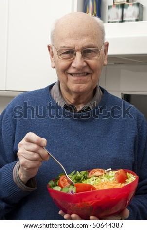 Senior man eating a healthy salad at the kitchen - stock photo