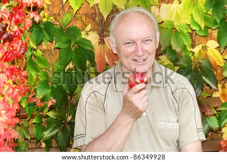 Senior man eating an apple in the garden