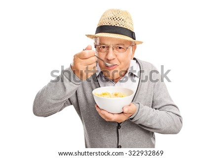 Senior man eating cereal with a spoon and looking at the camera isolated on white background - stock photo