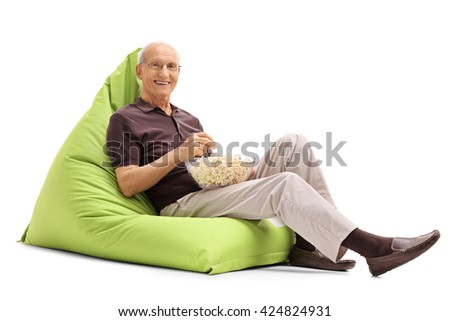 Senior man eating popcorn seated on a green beanbag and looking at the camera isolated on white background - stock photo