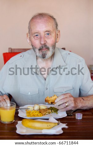 Senior man eating well balanced diet with medication tablets - stock photo