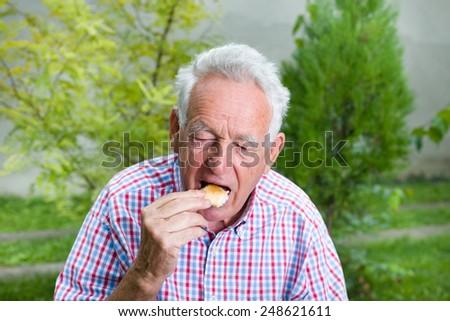 Senior man eating white bread in courtyard - stock photo