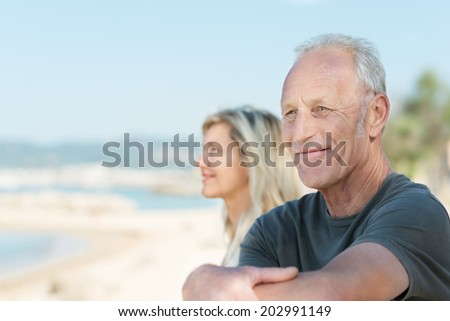 Senior man enjoying a relaxing day at the beach sitting with folded arms looking out over the ocean with a smile of pleasure - stock photo