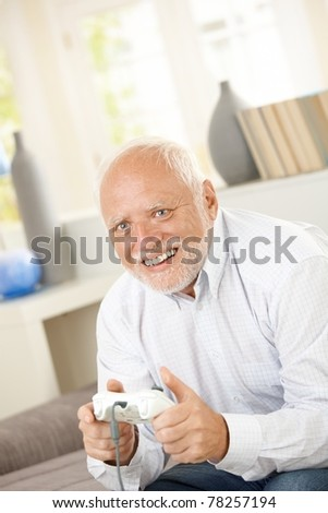 Senior man enjoying computer game, laughing, sitting at home. - stock photo
