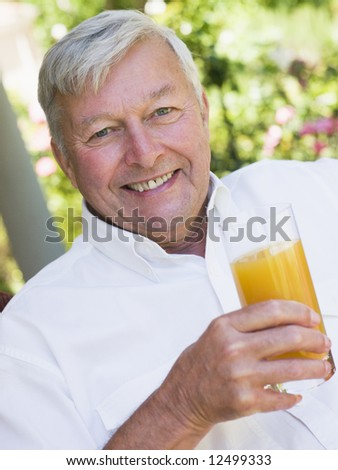 Senior man enjoying glass of orange juice sitting on garden seat - stock photo
