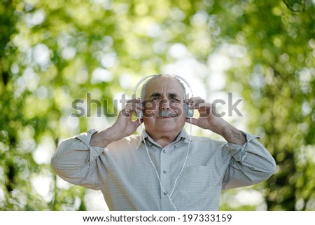 Senior man enjoying his music as he stands outdoors under the trees in the garden listening to his headphones, low angle view - stock photo
