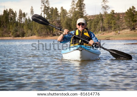 Senior Man Enjoying Kayaking on Lake - stock photo