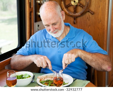 Senior man enjoys a healthy dinner of turkey, green beans and salad, in his motor home. - stock photo