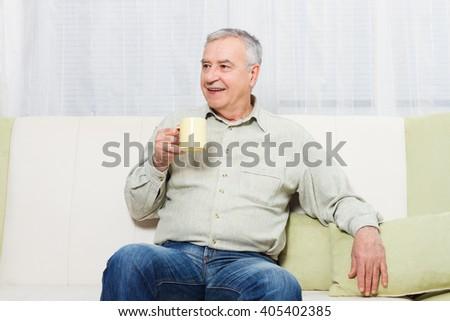 Senior man enjoys drinking coffee or tea at home.Senior man drinking coffee or tea - stock photo