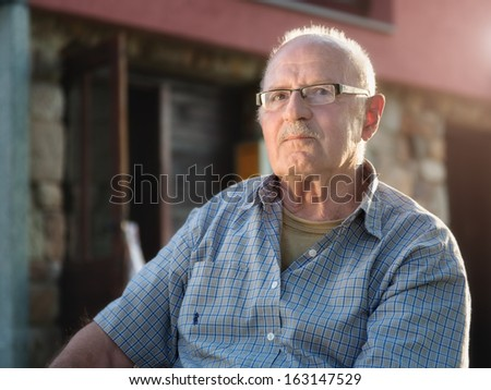 Senior man enjoys in front of his house at the early morning sunlight - stock photo