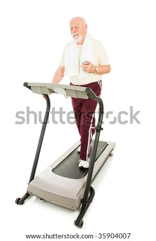 Senior man enjoys music on his mp3 player while he walks on the treadmill.  Full body isolated on white.