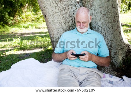 Senior man enjoys texting on his smart phone.  Wide view with room for text. - stock photo