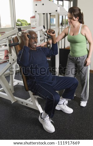 Senior man exercising in gym with trainer - stock photo