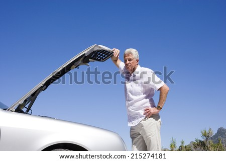 Senior man experiencing car trouble, looking at engine, leaning against open bonnet, thinking