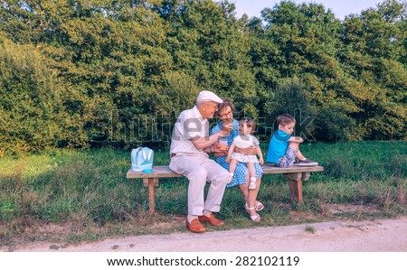 Senior man feeding with fruit puree to adorable baby girl while a jealous brother turns his back sitting in a bench outdoors. Grandparents and grandchildren relations concept. - stock photo