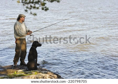 Senior man fishing from the lake shore. His curly haired retriever pet sits beside him.