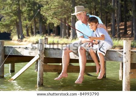 Senior man fishing with grandson - stock photo