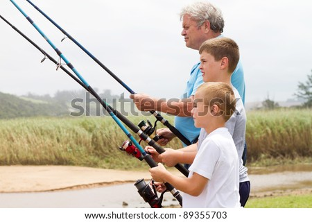 senior man fishing with his grandsons by the river - stock photo