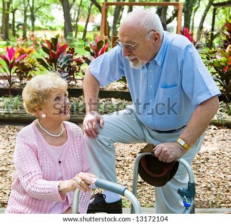 Senior man flirting with beautiful senior lady in the park. - stock photo