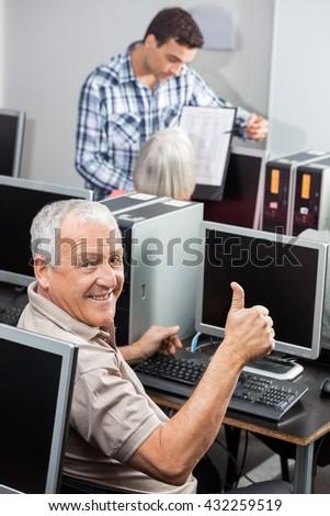 Senior Man Gesturing Thumbs Up At Computer Desk - stock photo