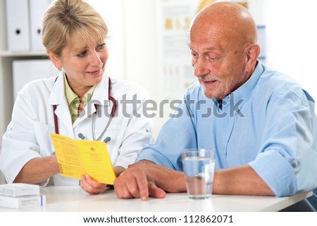 Senior man gets an international certificate of the vaccination from the doctor - stock photo