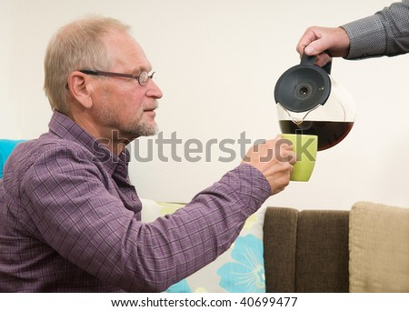 Senior man getting a refill of his cup of coffee.