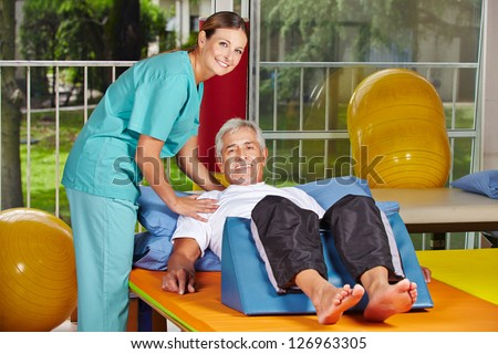 Senior man getting rehab at physiotherapy in nursing home - stock photo
