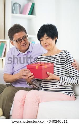 Senior man giving Christmas present to his wife