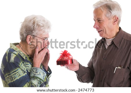 Senior man giving his wife a box of valentine chocolates; the wife looks a bit shocked - stock photo