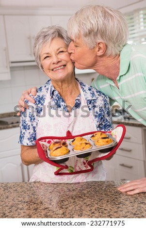 Senior man giving his wife a kiss at home in the kitchen - stock photo