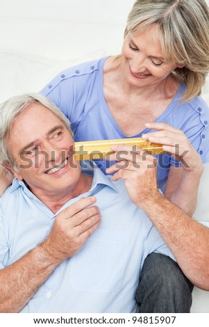Senior man giving woman a Valentines Day gift - stock photo